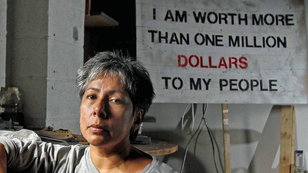 "Artist Rebecca Belmore poses in front of her sign ""I Am Worth More/Than One Million/Dollars/ To My People, "" in her studio in Vancouver."
