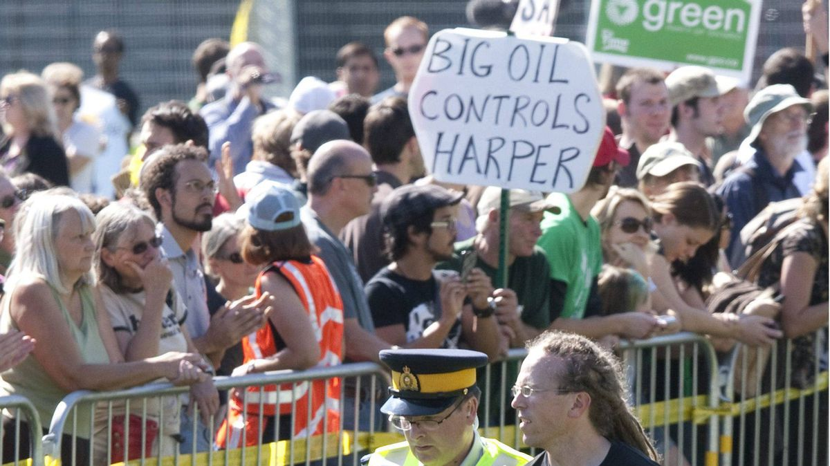 A protester is led away by police after crossing a barricade during a protest against the Keystone XL pipeline on Parliament Hill in Ottawa, Monday September 26, 2011.