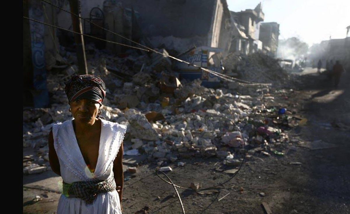 A woman stands amidst the rubble of the destroyed commercial district of downtown Port-au-Prince.