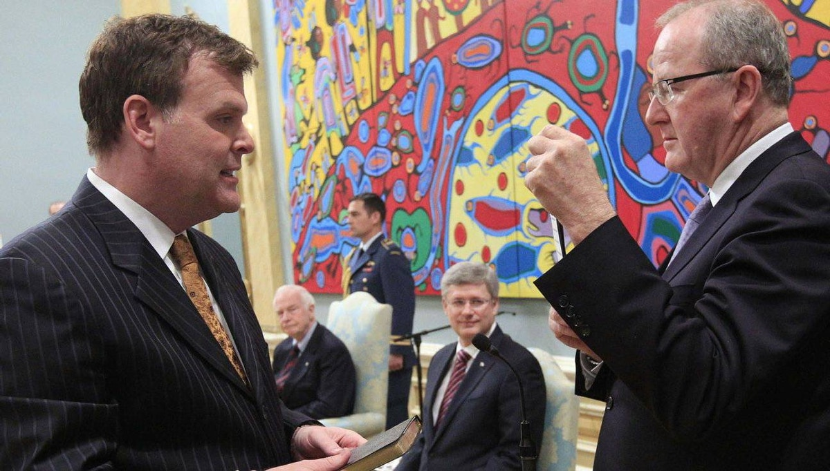 John Baird (L) is sworn-in as Canada's Minister of Foreign Affairs as Prime Minister Stephen Harper (C) and Governor general David Johnston look on during a ceremony at Rideau Hall in Ottawa.