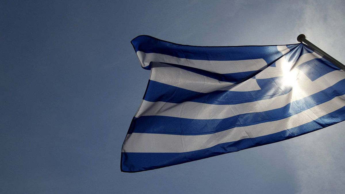 A Greek flag flies in the wind at a park in central Athens.