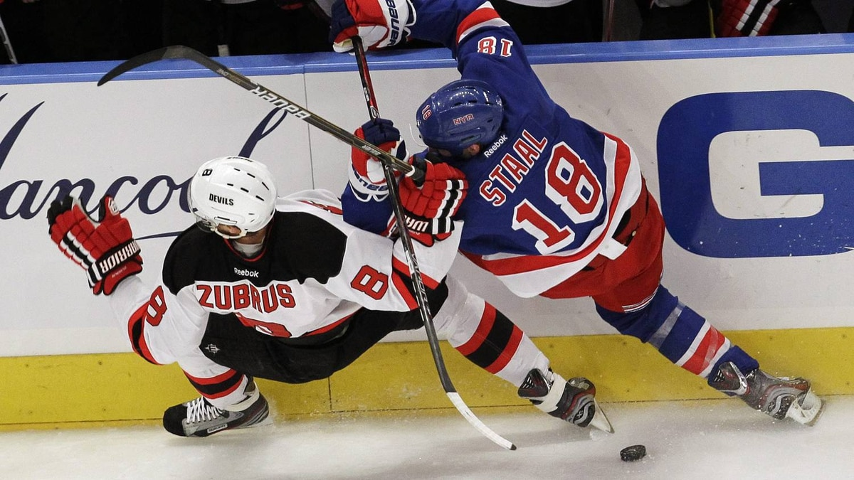 New Jersey Devils' Dainius Zubrus (8), of Lithuania, and New York Rangers' Marc Staal (18) collide while competing for the puck. (AP Photo/Julio Cortez)