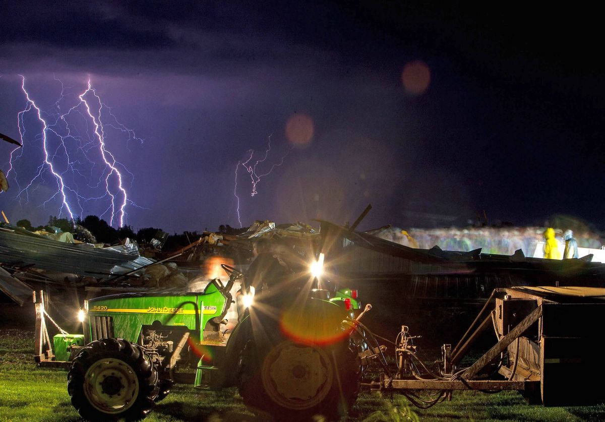 Lightning strikes in the distance as volunteers (on right) help rescue more than a thousand turkeys from a destroyed barn on the property of a farmer who did not wish to be identified east of Wayland, Iowa.