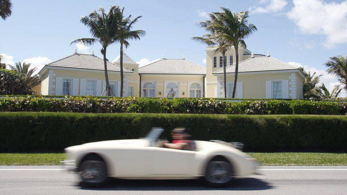 A car makes its way past Conrad Black's home in West Palm Beach, Fla.