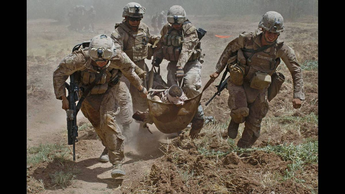 U.S. Marines carry a comrade wounded by an improvised explosive device (IED) to a waiting medevac helicopter, near the town of Marjah in Helmand Province, August 21, 2010.
