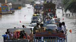 Trucks and cars cross through a flooded highway in Muzaffargrah, in central Pakistan on Sunday, Aug. 22, 2010.