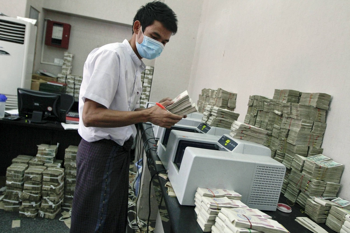 A bank employee counts Myanmar kyat banknotes: More than two decades of isolation and poor government have left Myanmar the poorest country in Asia besides Afghanistan.
