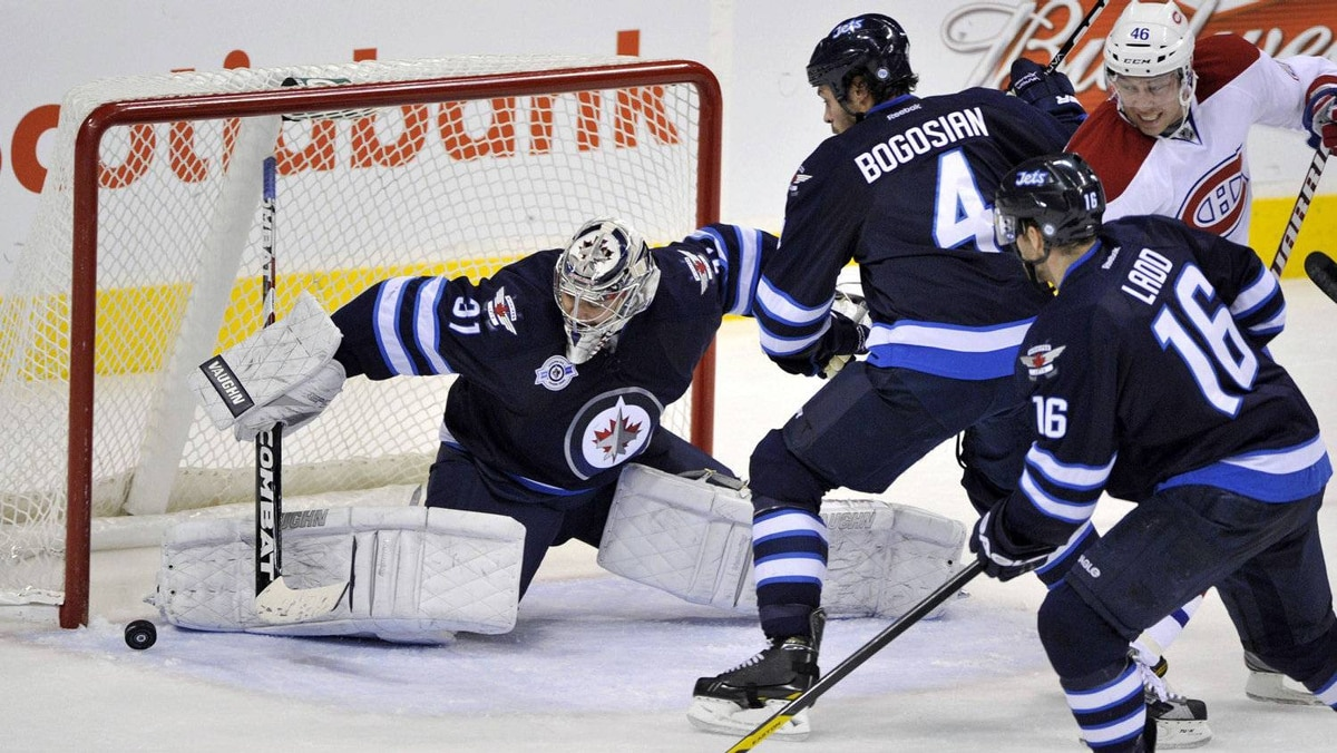 Winnipeg Jets goaltender Ondrej Pavelec makes a save on Montreal Canadiens' Andrei Kostitsyn (46) as Jets' Zach Bogosian (4) and Andrew Ladd (16) watch the rebound during the second period of their NHL hockey game in Winnipeg December 22, 2011.