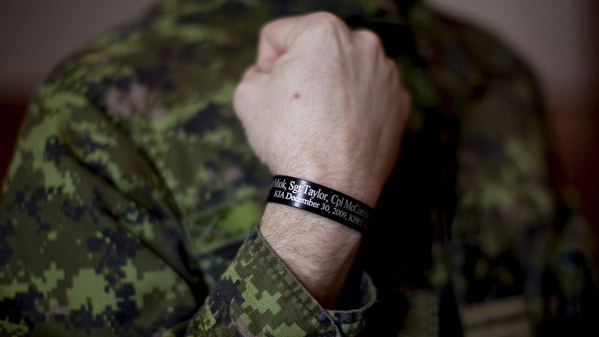 Capt. Darryl Watts, in Calgary, shows the wristband that bears the names of those killed during a IED explosion in Afghanistan Dec 30, 2009.
