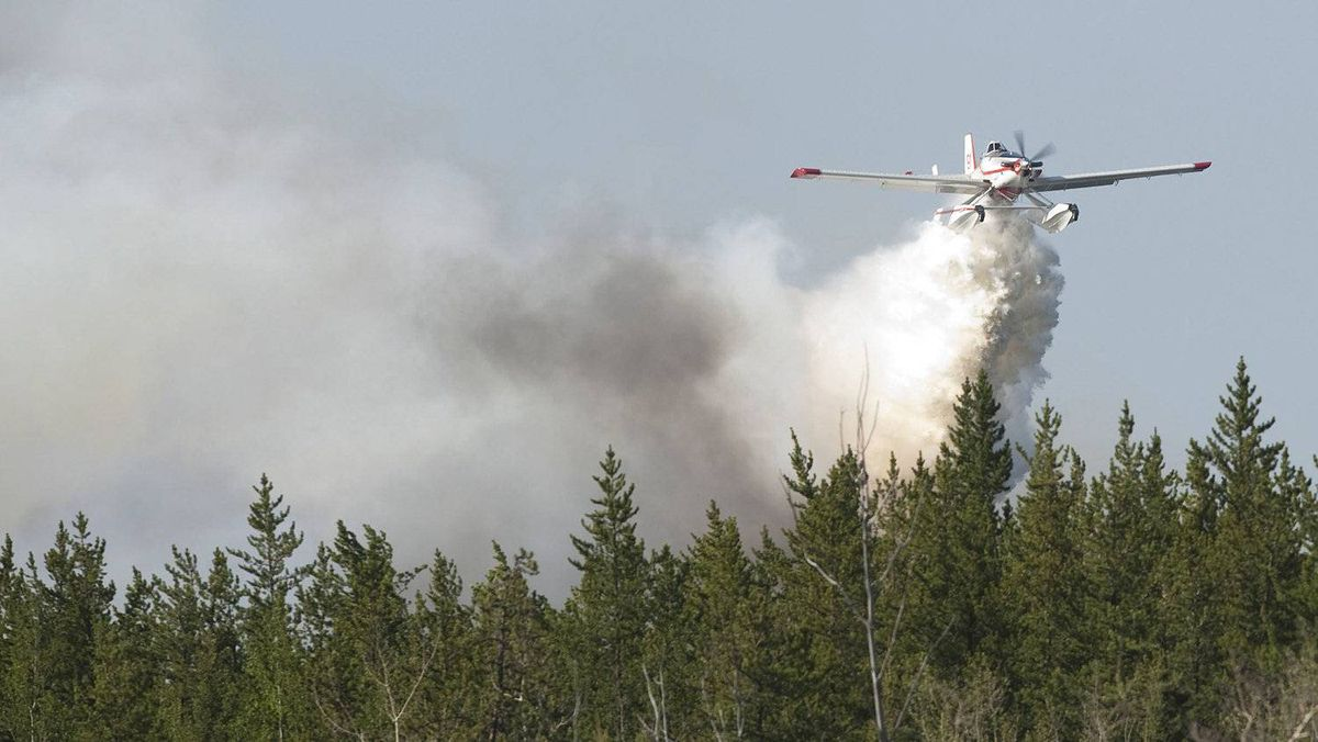 A water bomber drops its load on a wildfire northeast of Edmonton in May. Intact's results were hurt by claims related to such fires.