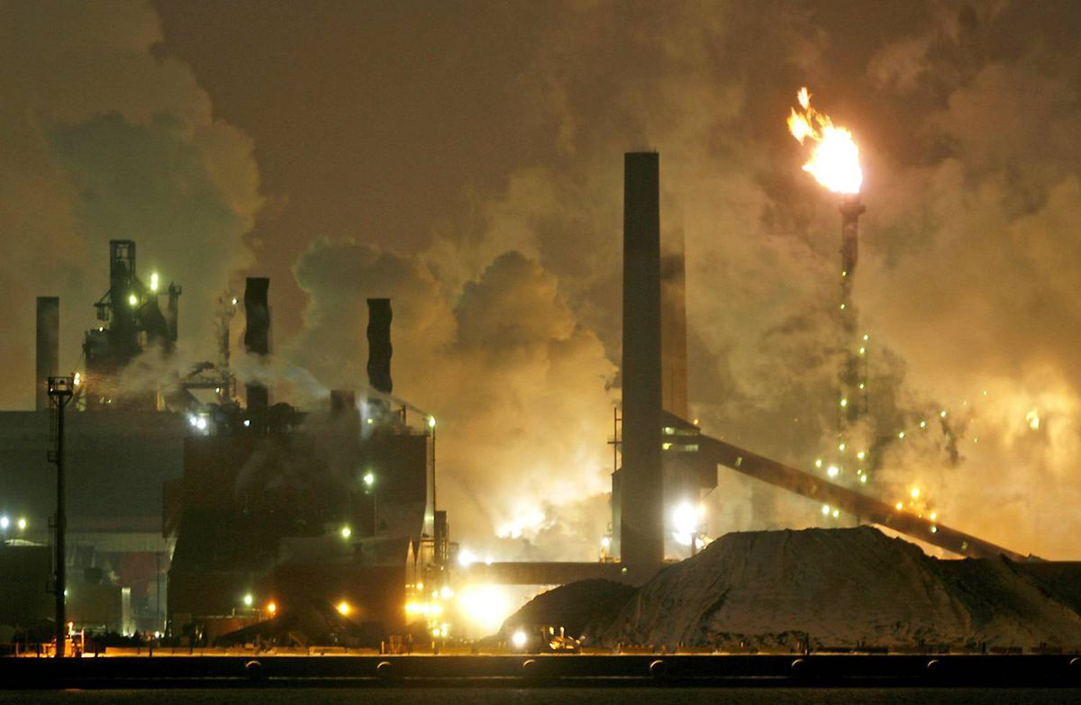 Waste gases burn as smoke and steam belch from steel mills in Hamilton on February 1, 2007.