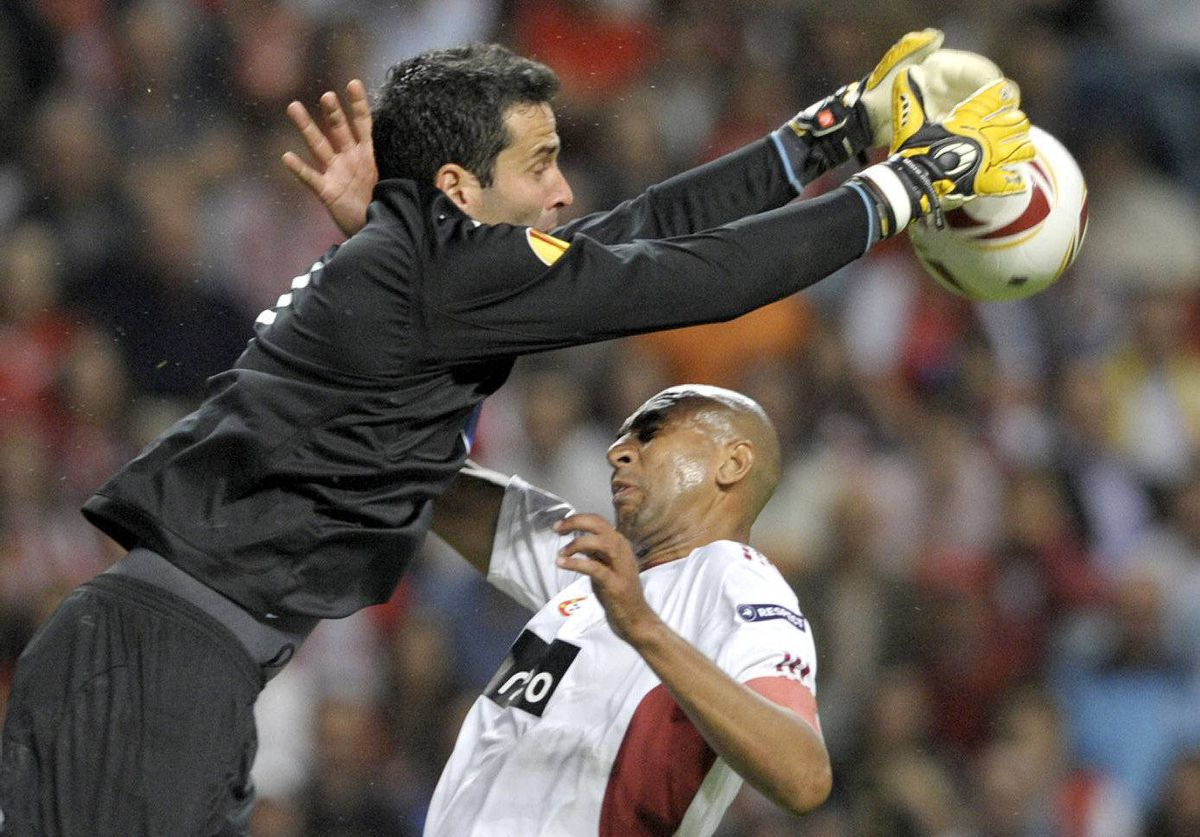 "SC Braga's Brazilian goalkeeper Artur Moraes (L) stops the ball next Benfica's Brazilian defender Anderson Silva ""Luisao"" (R) during their UEFA Europa League semi-finals football match at the Municipal Stadium in Braga"