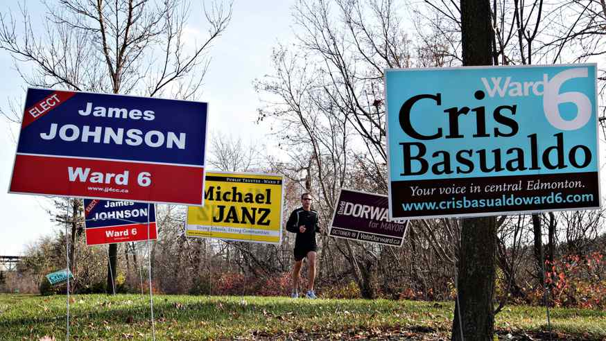 A jogger runs past campaign signs along River Valley Road in Edmonton, Alta., Oct. 17, 2010. Voters will head to the polls for municipal elections across Alberta on Oct. 18.
