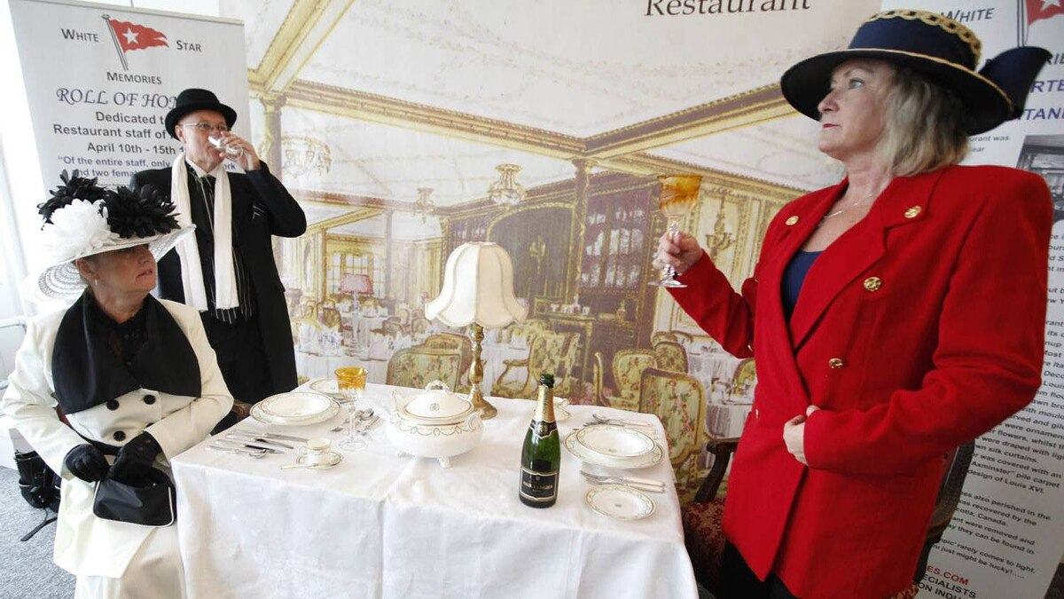 Carmel Bradbam and Andreas Stovic , both at left, from Adelaide, Australia drink champagne as they sit in a mock up of a first class dinning table of the Titanic in the check in area for the MS Balmoral's Titanic memorial cruise in Southampton, England, Sunday, April 8, 2012.