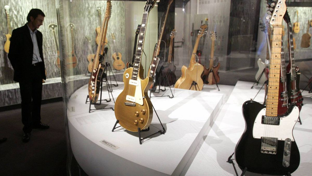 A 1963 Fender Telecaster Custom guitar belonging to John Lennon, right, is displayed in Paris in October, 2006.