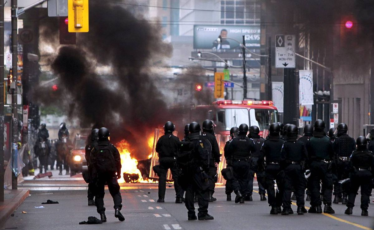 Riot police move towards a police car set on fire by anarchist demonstrators in the midst of protests during the G20 summit in Toronto