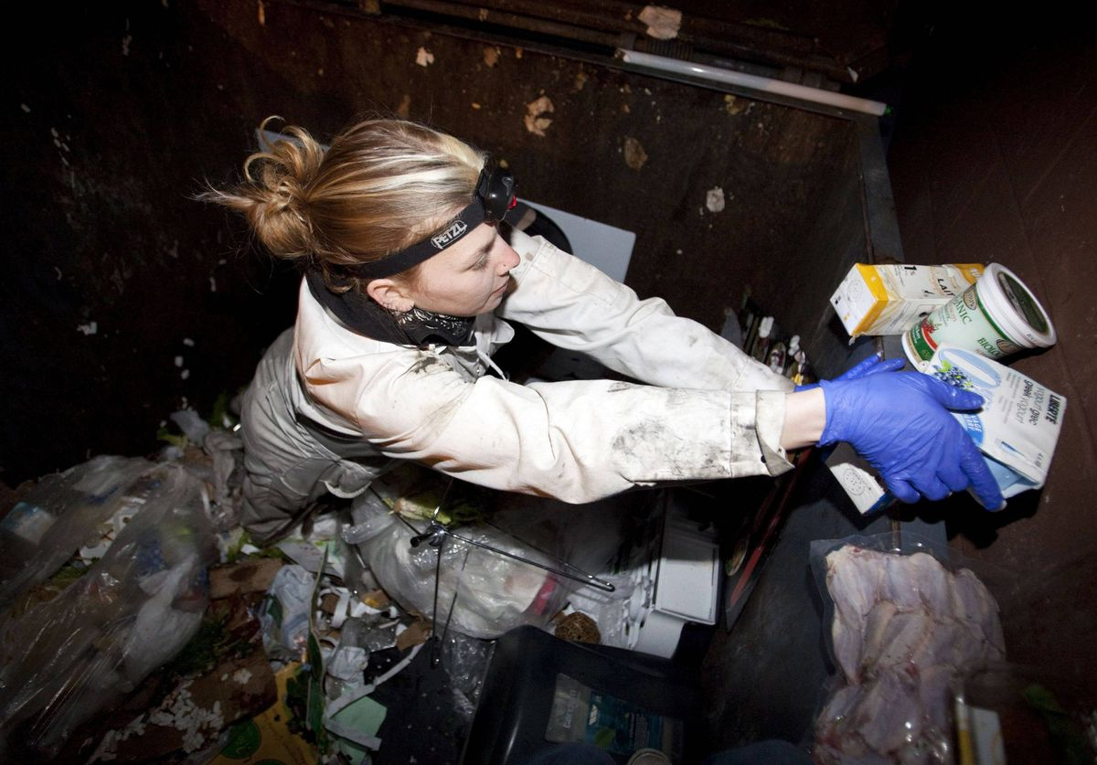 Anna-Rae Douglass, 23, a practising 'freegan', sorts through a dumpster for edible food behind an organic grocery store in Coquitlam.