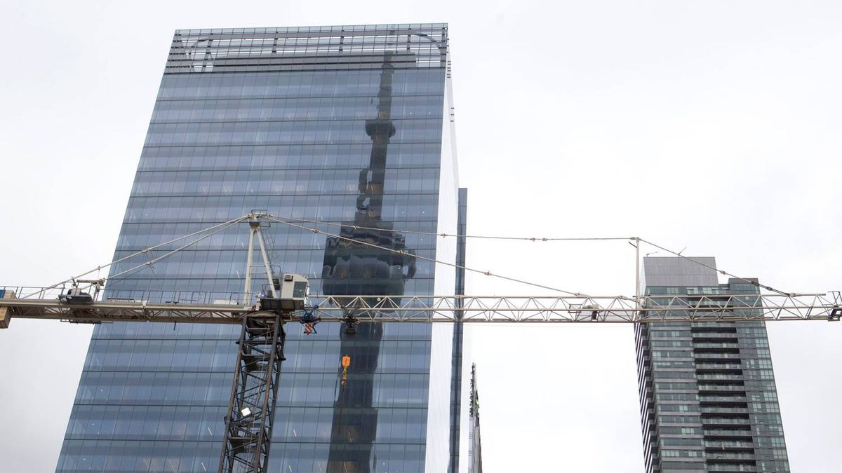 The CN tower is reflected in a high rise building behind a construction crane in downtown Toronto on Saturday, February 4, 2012. The condo explosion is changing the shape and culture of Canada's cities.