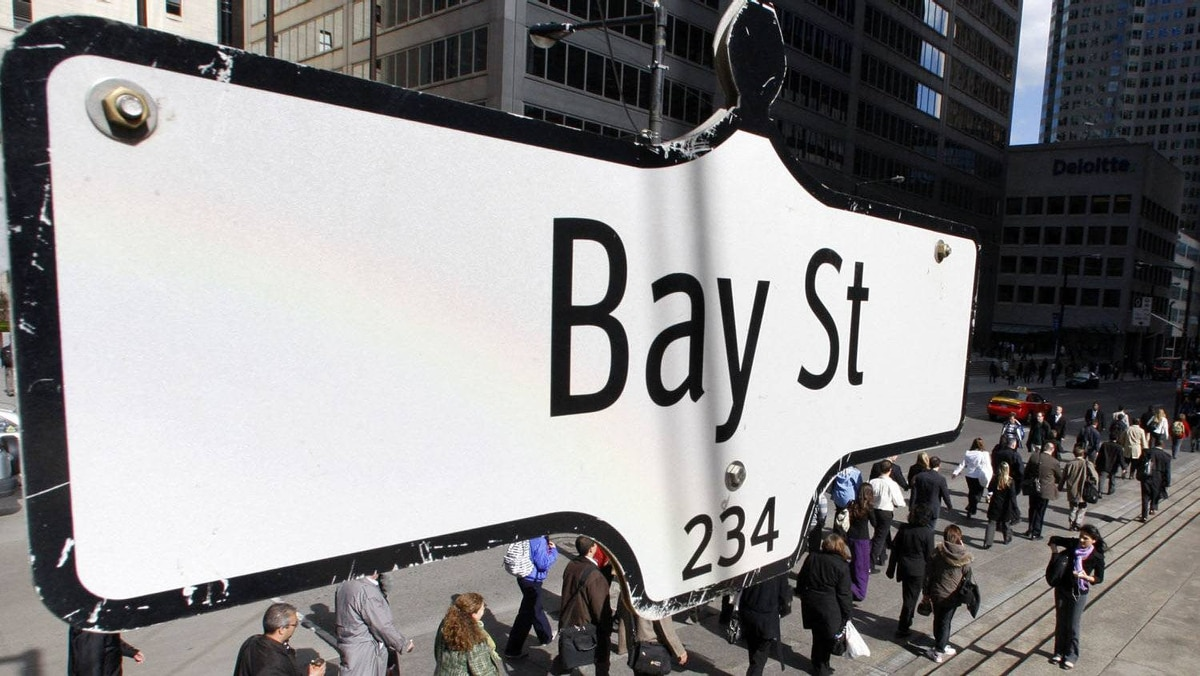 The Bay Street sign is shown in the heart of the financial district as people walk by in Toronto.