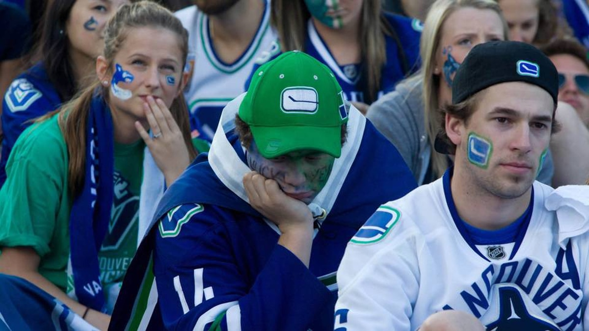 Fans react as they watch TV coverage of the Vancouver Canucks playing the Boston Bruins in Game 4 of the Stanley Cup final in downtown Vancouver.