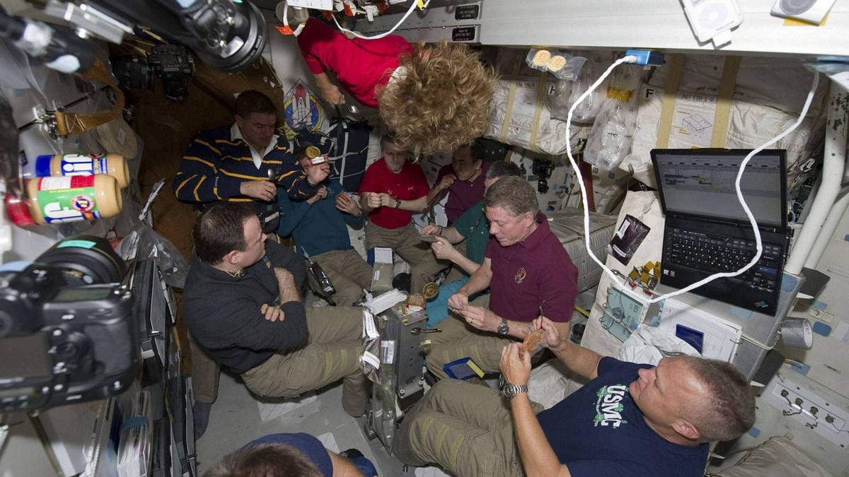 Space shuttle Atlantis and International Space Station astronauts gather for one of the final meals shared between shuttle and station crews aboard the orbiting laboratory in this photo provided by NASA and taken July 14, 2011.