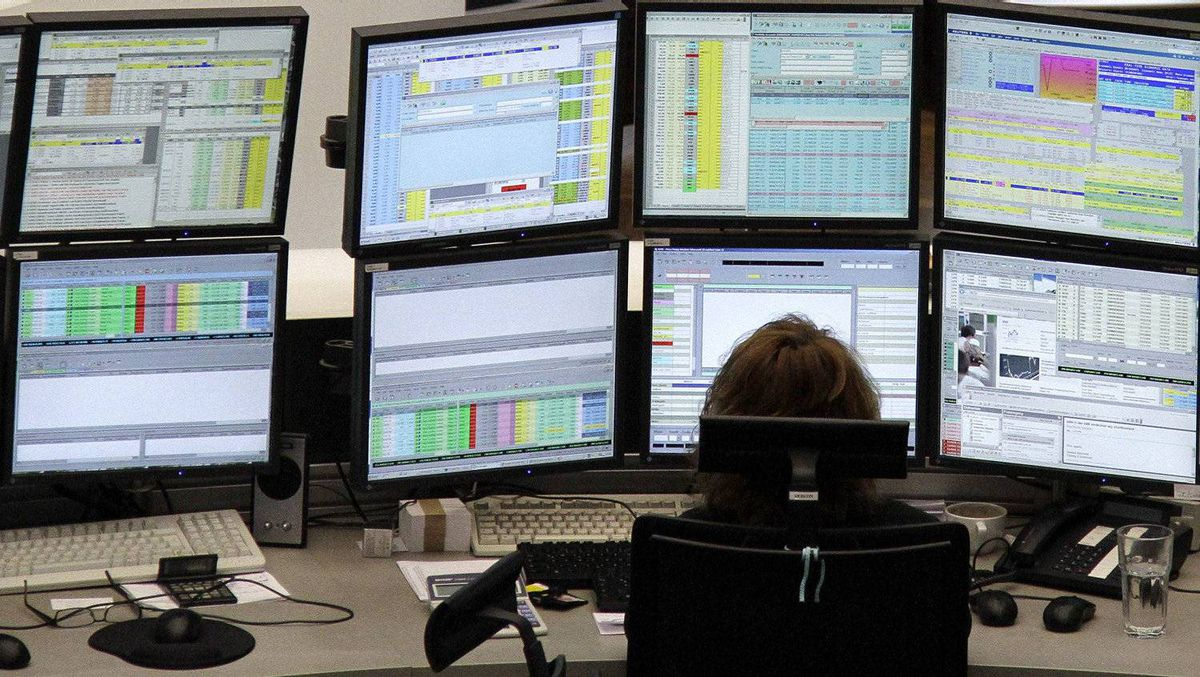 A trader is pictured at her desk in front of screens at the Frankfurt stock exchange.