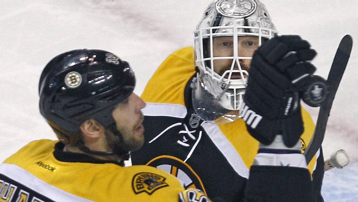 Boston Bruins goalie Tim Thomas, right, watches as defenseman Zdeno Chara knocks the puck away against the Washington Capitals during the second period of Game 2 of an NHL hockey Stanley Cup first-round playoff series in Boston, Saturday, April 14, 2012. AP Photo/Charles Krupa)