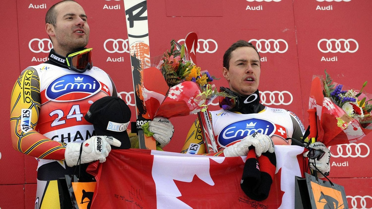 Canada's Jan Hudec, left, celebrates on the podium with third placed fellow-countryman Erik Guay, after winning an alpine ski, men's World Cup downhill, in Chamonix, France, Saturday, Feb. 4, 2012. (AP Photo/Mario Curti)