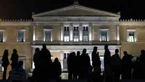 Protesters stand in front of the parliament in Athens Friday as law makers prepare for a confidence vote on the government of Prime Minister George Papandreou.