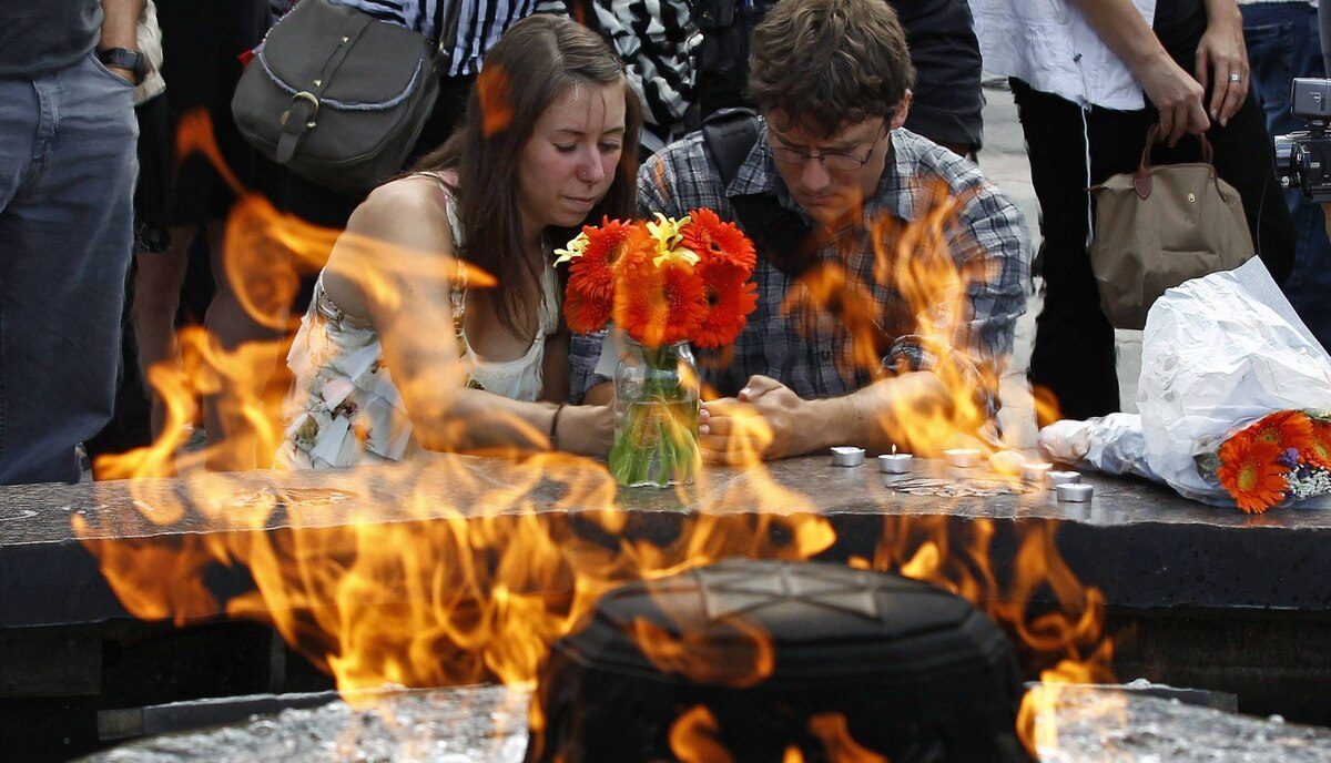 People pay tribute to Jack Layton in front of the Centennial Flame on Parliament Hill in Ottawa.
