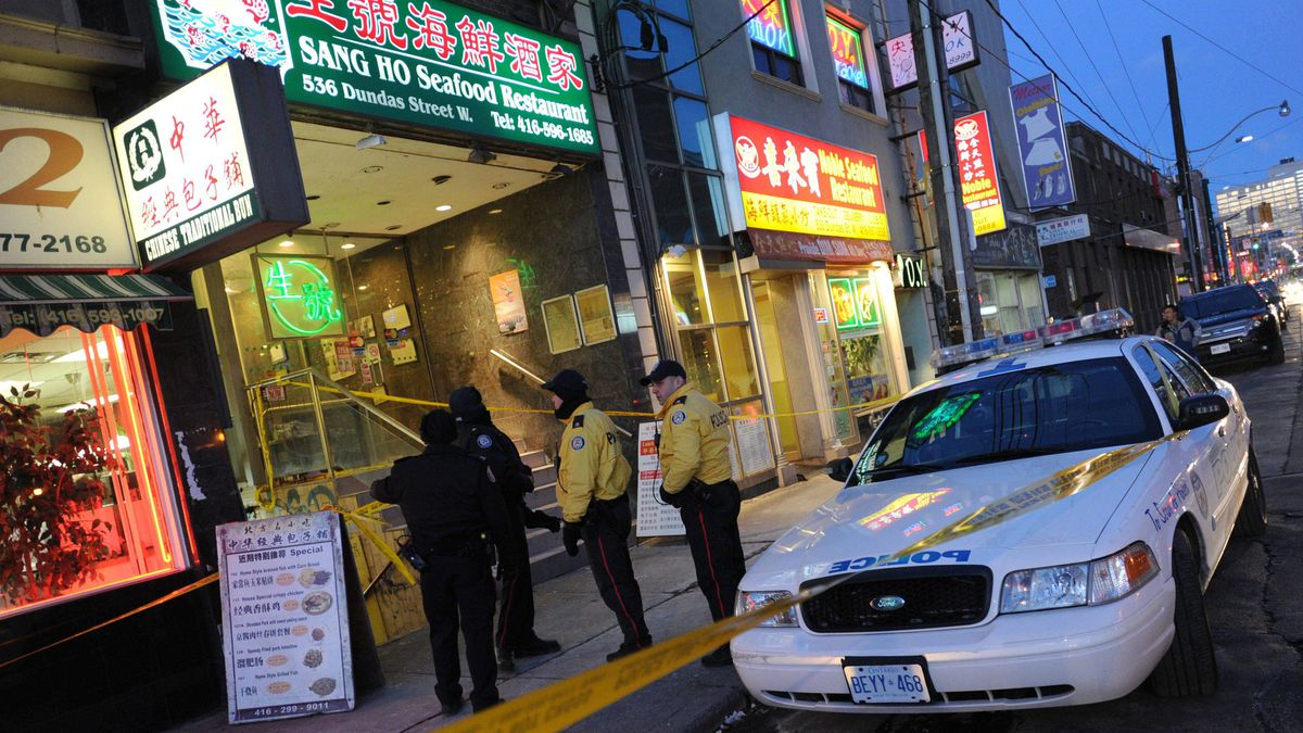 Police investigate at a restaurant in Toronto's Chinatown on Wednesday, Dec. 28, after a woman was taken to hospital suffering from stab wounds to the neck.