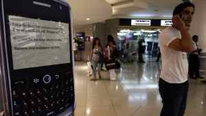 A man speaks on his mobile phone as he stands next to a display of a BlackBerry at a shopping mall in Dubai August 1, 2010.