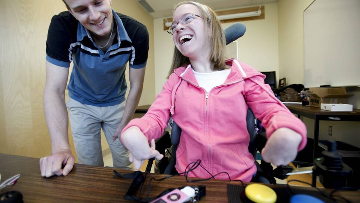 Corinne Eisenstein,17, who has cerebral palsy and is a quadriplegic, listens to her ipod music player through mini speakers as Carl Spani, the designer of the CanPlay podWiz device by CanAssist , watches over her shoulder, at the University of Victoria Thursday.