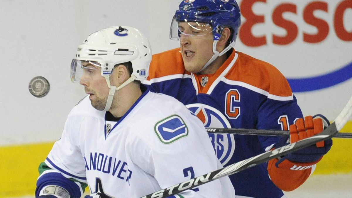 Edmonton Oilers' Shawn Horcoff, right, battles with Vancouver Canucks' Kevin Bieksa, during the first period of the NHL hockey game in Edmonton on Sunday, February 19, 2012. The Canucks won 5-2. THE CANADIAN PRESS/John Ulan