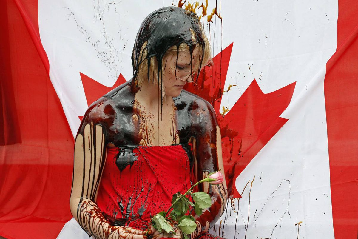 A protester sits in front of a Canadian flag as she is doused in molasses during an anti-Alberta-oil-sands protest on Parliament Hill on Sept. 8, 2010.