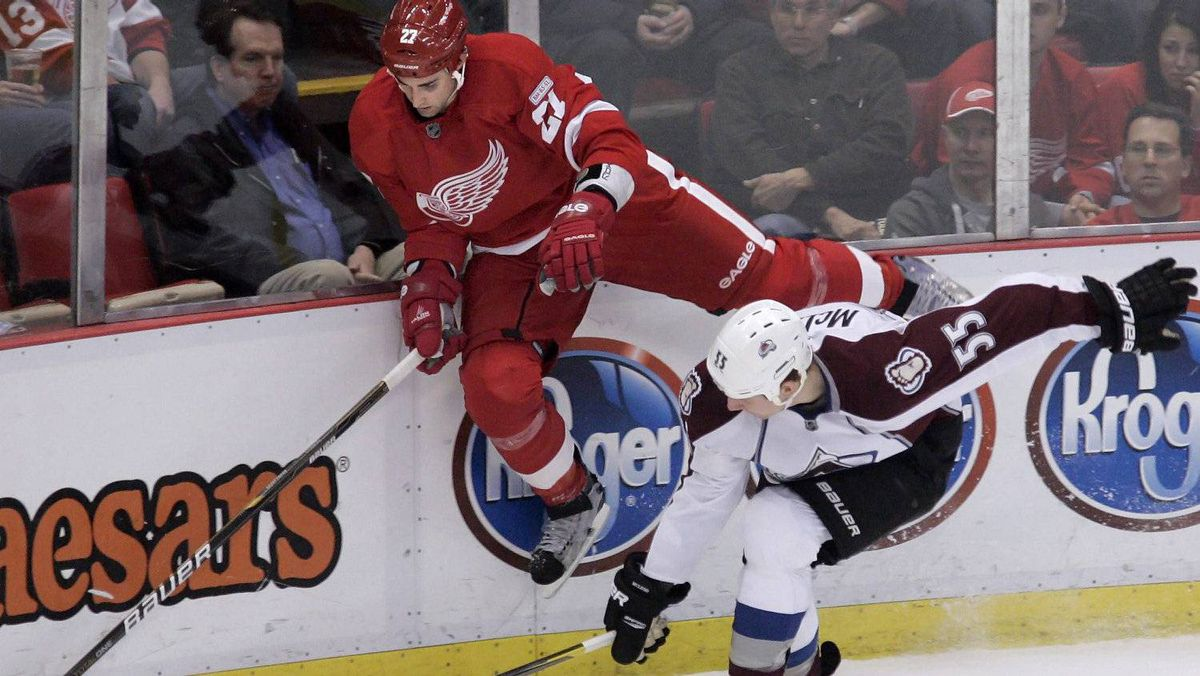 Detroit Red Wings' Kyle Quincey (27) goes up against the boards to chase the puck against Colorado Avalanche's Cody McLeod (55) in the second period of an NHL hockey game Saturday, Feb. 25, 2012, in Detroit. The Avs won 4-3. (AP Photo/Duane Burleson)