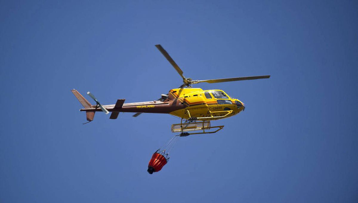 A helicopter works to contain a forest fire as it tore through the community of Slave Lake Alberta.
