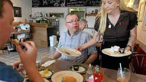 Greg Cook, glasses, from Kitchener likes to share a meal with friends but he doesn't want to share the bill. Cook says it's a growing trend within his circle of friends to ask separate bills no matter how many of them are in the party. Janet Schwartzentruber takes up the dishes before passing out the separate bills to Cook and his friend Brian Kean in Barnes Casual Dining Restaurant in Kitchener on July 28, 2011.