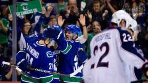 Vancouver Canucks' Mason Raymond, from left, Daniel Sedin, of Sweden, and Henrik Sedin, of Sweden, celebrate Daniel Sedin's goal as Columbus Blue Jackets' Vinny Prospal, right, of the Czech Republic, skates to the bench during the first period of an NHL hockey game in Vancouver, B.C., on Saturday March 17, 2012.