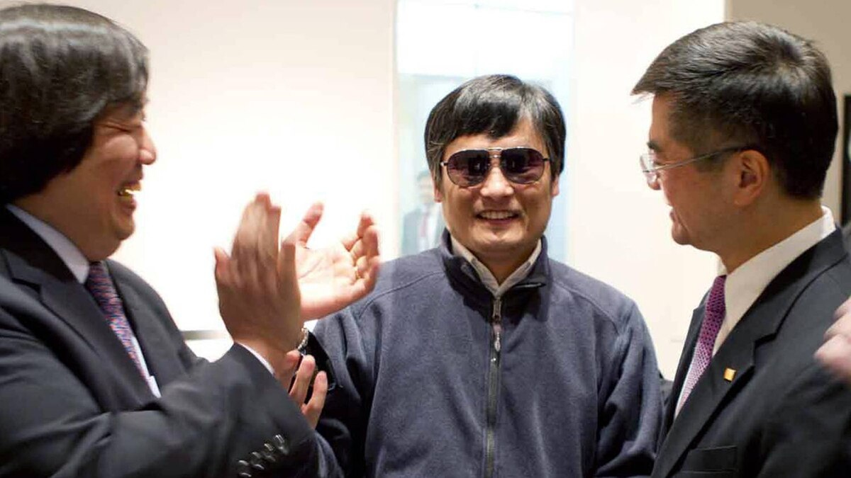 A handout photo from US Embassy Beijing Press office shows blind activist Chen Guangcheng (C) shaking hands with U.S. Ambassador to China Gary Locke (R), in Beijing, May 2, 2012.