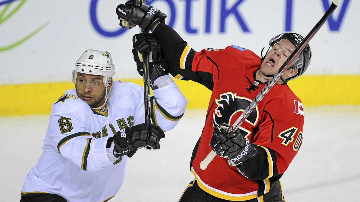 The Calgary Flames' Alex Tanguay gets hit with the high stick of the Dallas Stars' Trevor Daley in Calgary.