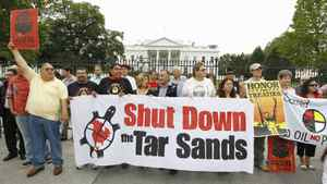 Native demonstrators hold up signs in front of the White House in Washington, Friday, Sept. 2, 2011, to protest the Keystone XL Pipeline project in the U.S., and the tar sands development in Alberta.