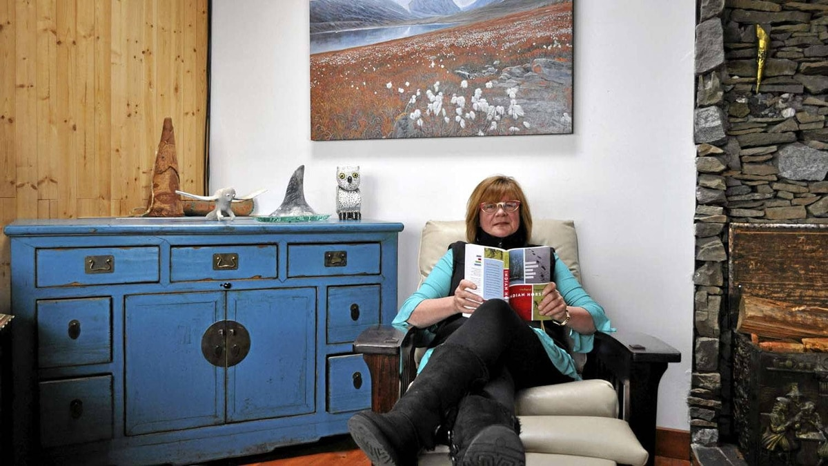 Shelagh Rogers reading in her home.
