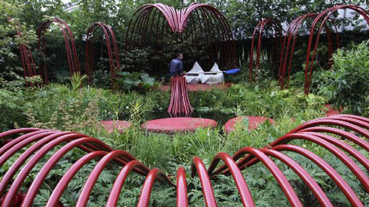 A gardener works in the British Heart Foundation Garden at the Chelsea Flower Show in London, Monday, May 23, 2011. The show garden inspired by the human heart in a pop art style highlights the healing properties of plants.