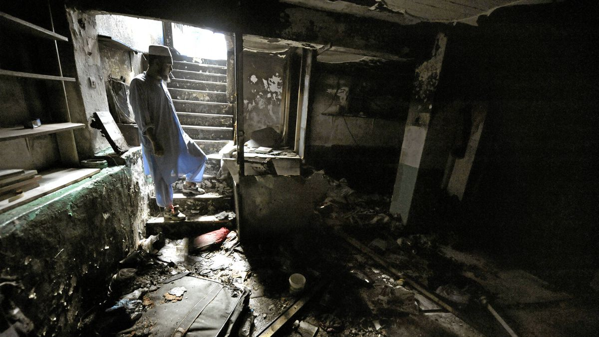 A muslim man looks at the damage done to a makeshift mosque after unknown assailants broke through the windows of the basement flat early on May 23, 2009 and set it on fire in Athens.