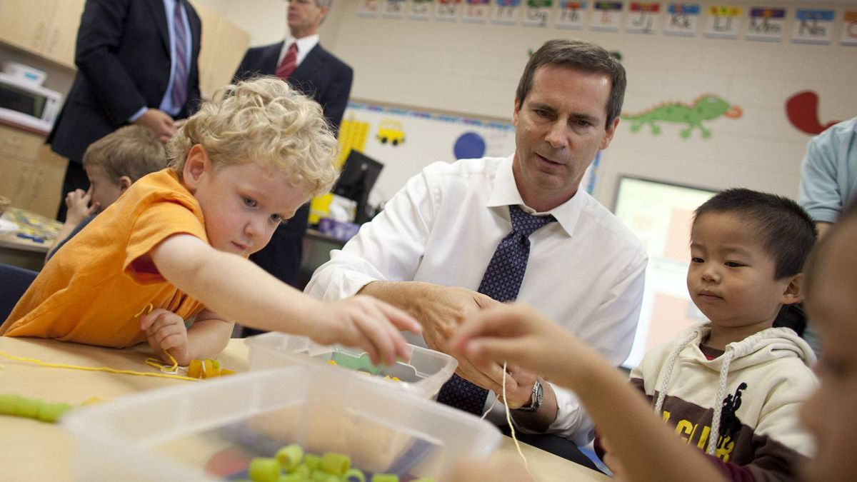 Premier Dalton McGuinty builds necklaces with Nathan Skinner, 3, left, and Alex You, 4, in a full day kindergarten class at Stoney Creek Public School in London, Ontario, October 8, 2010.
