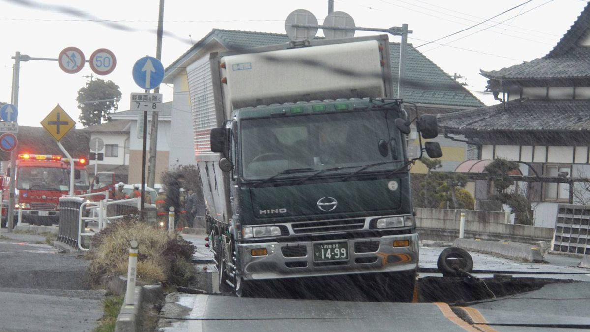 A truck remains stranded on a road damaged by a powerful earthquake in Iwaki city, Fukushima prefecture, Japan. Kyodo News/AP