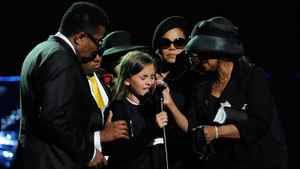 Supported by her family, Paris Jackson, centre, speaks during the Michael Jackson public memorial service held at Staples Center on Tuesday in Los Angeles.