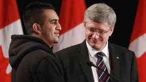 Prime Minister Stephen Harper, right, stands with former gang member Tanbir Uppal after announcing the renewal of the Youth Gang Prevention Fund. in Surrey, B.C., on Tuesday March 15, 2011.