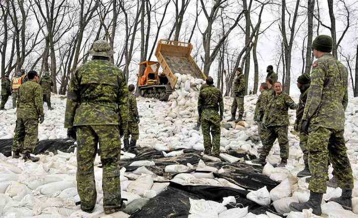 Members of the Princess Patricia's Canadian Light Infantry wait for sandbags to be unloaded as they shore up up a dike along an Assiniboine River near Poplar Point, Manitoba, May 12, 2011.